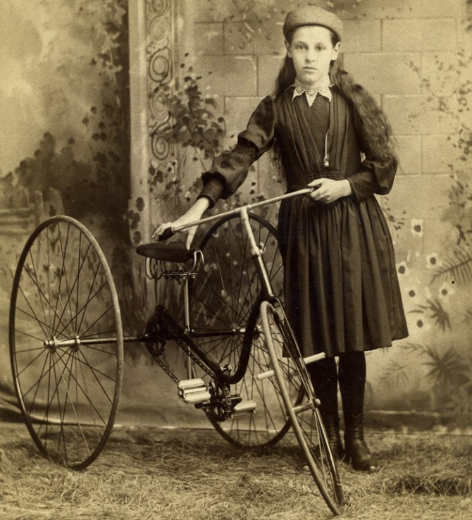 Girl stands with tricycle