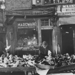 tables with piles of shoes in front of hardware store