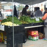 shoppers examining piles of vegetables on tables