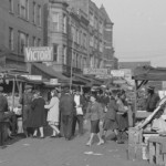people, carts, and goods in a crowded street scene