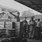 Workers standing next to boxes of produce