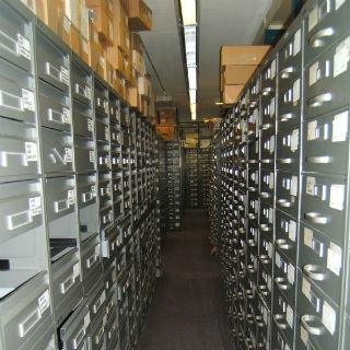 view down a row of filing cabinets with cardboard file boxes piled on top