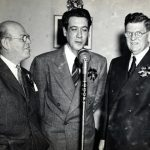 Mayor Edward J. Kelly (right) and State Street Council President David Mayer, Jr. looked on as Douglas Beattie, Basso of the Chicago Opera Company, opened the State Street Council's broadcasting of Christmas music for shoppers, 1940. Source: Special Collections, Chicago Loop Alliance Collection, Oversize Box 2, Folder 4.