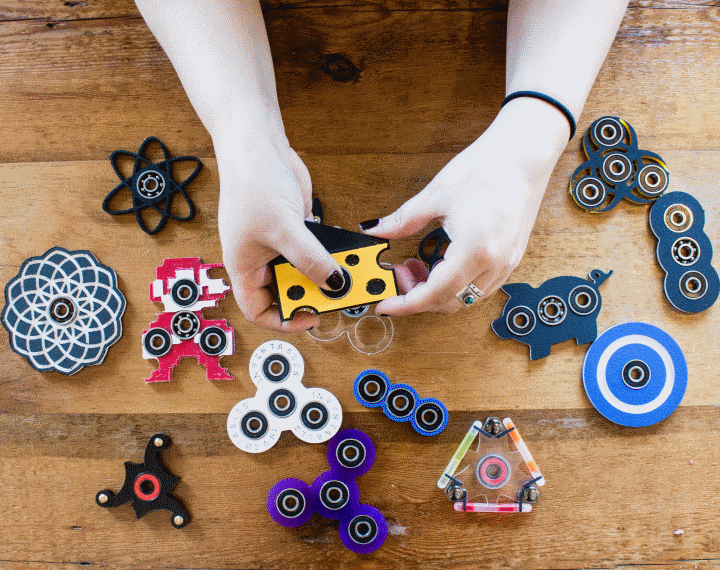 A pair of hands holds small objects called fidget spinners. Additional fidget spinners of different shapes and colors lay on a tabletop.