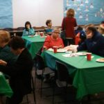 people gather around five small tables