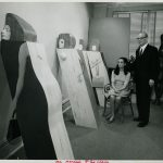 Marisol Escobar sits and Edward H Weiss stands; both look toward Women Leaning.