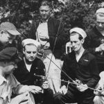 Seven veterans, some in uniform, holding fishing poles