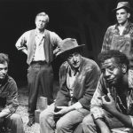 five men in rugged clothing pose on a stage