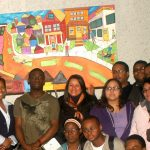 teens standing in front of a colorful painting of houses