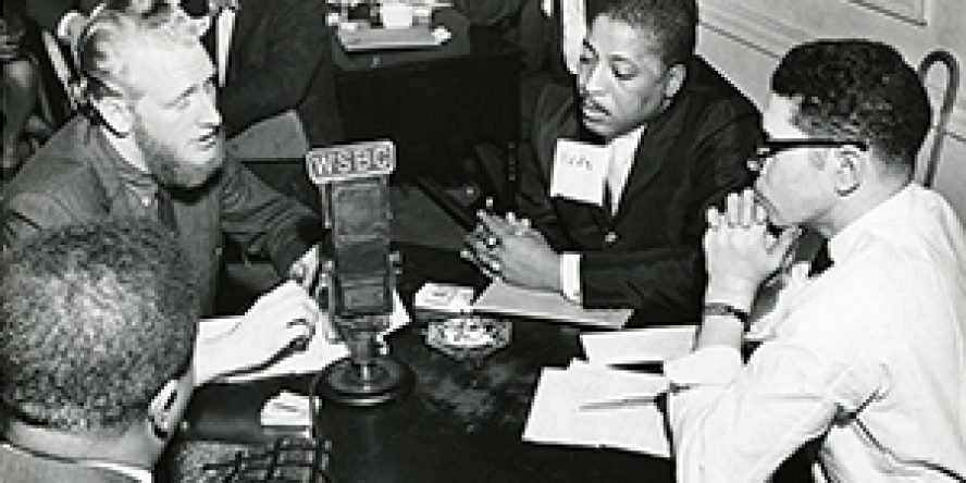 Activists and reporter gather around WSBC microphone
