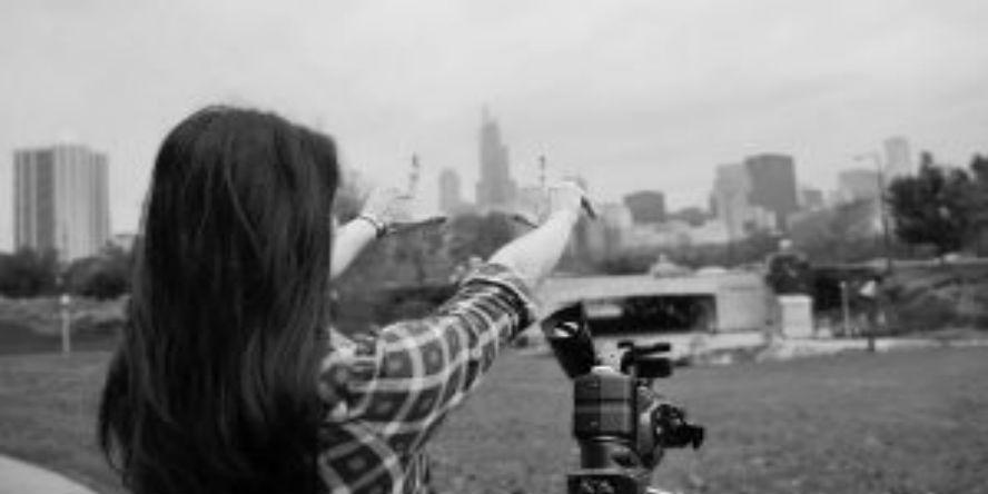 Woman sets up video camera on Chicago skyline