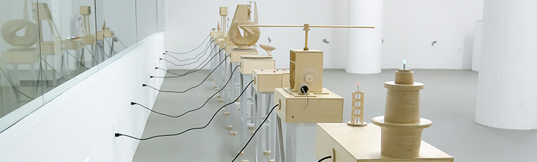 Tables with wooden sculptures, each with a cord plugged into a wall