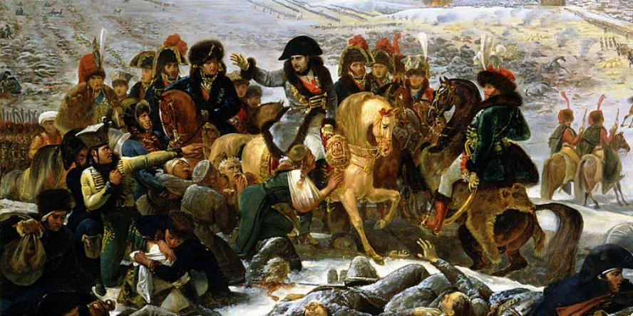 Napoleon on a white horse surrounded by his men as well as bodies on the battlefield