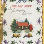 log cabin surrounded by trees with a needlepoint boarder