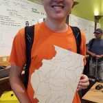 Man holding plywood in the shape of Illinois
