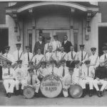 band members holding their instruments in front of a building