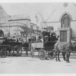 group of boys in two horse drawn wagons