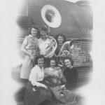 six high school girls holding brass musical instruments