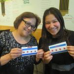 Made in the Maker Lab: Two patrons holding vinyl decals of the Chicago flag.