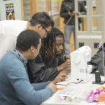 3 teens gather around a sewing machine