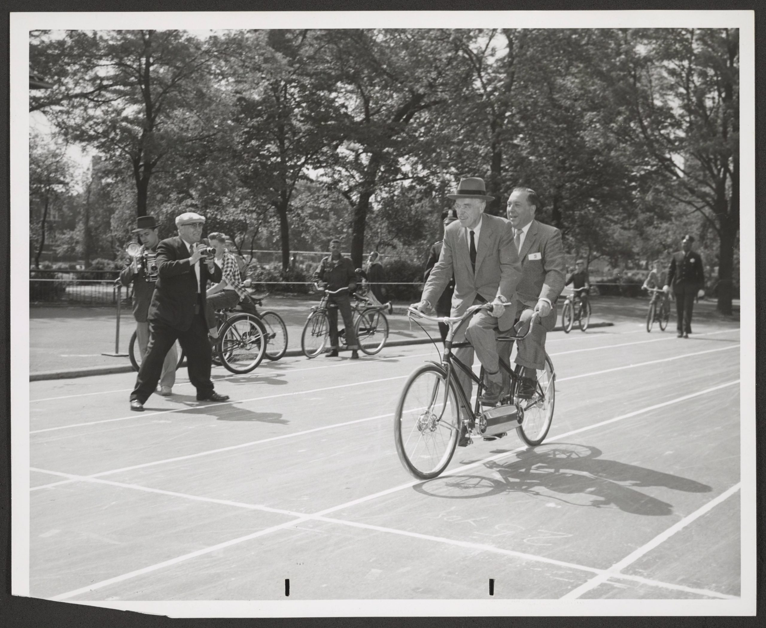 2 men in suits on tandem bike as photographer takes photos