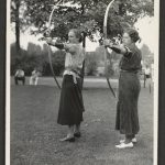 Two women in a park hold bows and arrows, ready to shoot
