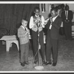 Three boys dressed in suits and vests stand at a microphone and play recorders. Adults watch from off stage.