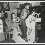 A boy and two younger girls ride a large hobby horse. Behind them is a cabinet full of toys and a toy tea set.