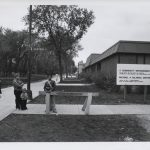 Crossing guard and children stand in front of building; people walk in the background