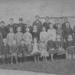 Class picture with group of students in three rows and teacher Lydia Newcomb with arms folded