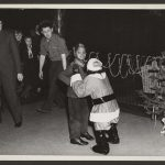boy looking surprised when approached by chimpanzee dressed in santa suit and adults look on