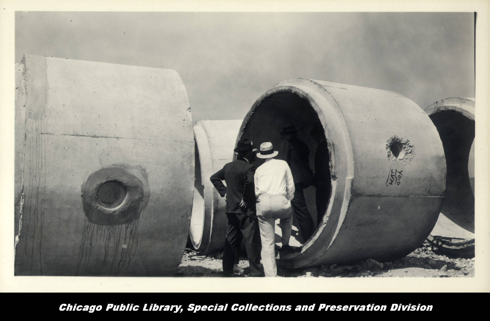 2 men looking in pipe taller than them