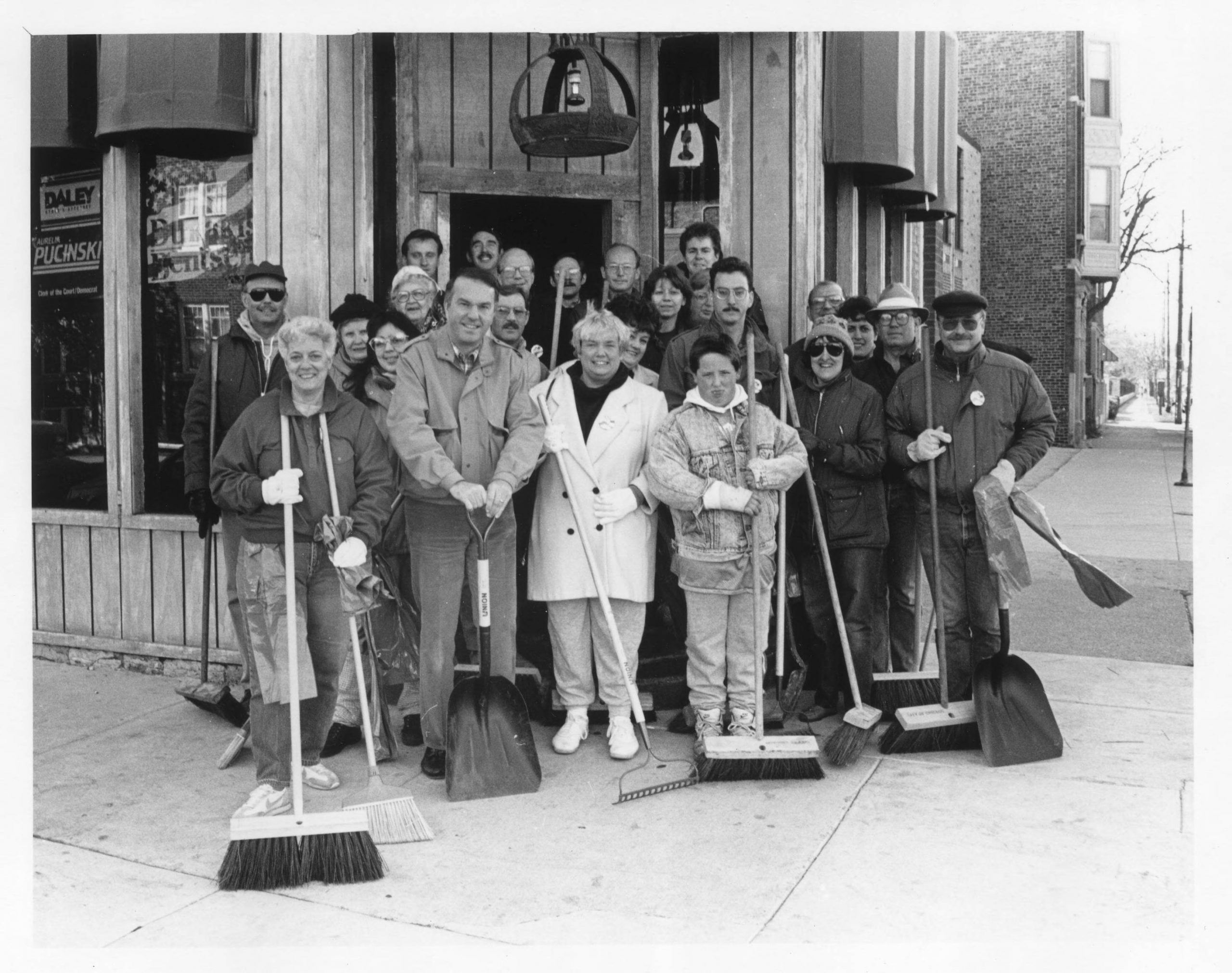 People with shovels and brooms in front of business