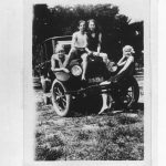 4 people pose on car