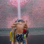 Kids in bathing suits under fountain spray