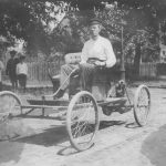 Man driving early-model car