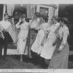 Man holding American flags while 5 women salute