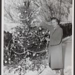 woman decorating a Christmas tree with garland