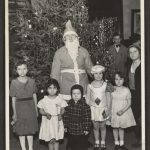 children pose with Santa in front of a Christmas tree