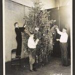 three boys decorate a Christmas tree