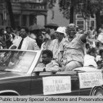 2 men sit on the back of a convertible driving through a parade