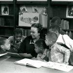 Children with books gather around woman