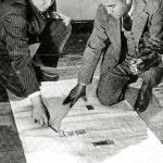 2 men kneel by large document