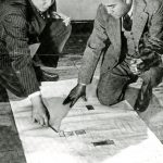 2 men kneel by large document