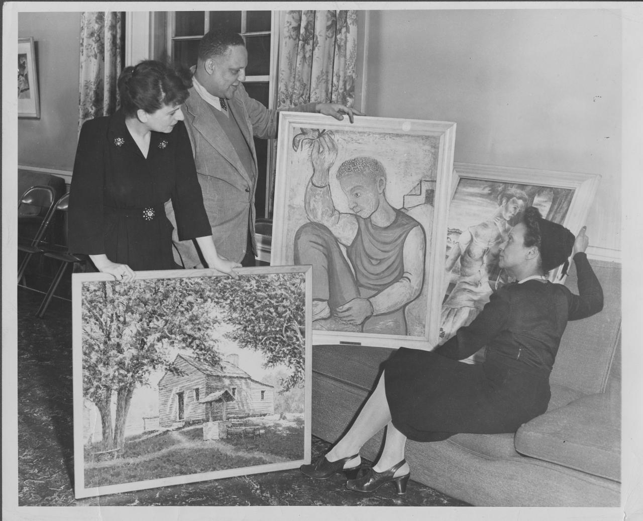 3 people look at artwork