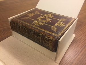 Image shows a brown calf leather binding with extravagant gold tooling on its cover and spine. The book is sitting inside an open drop spine enclosure. A pressure lid is hinged open from the wall enclosing the fore edge of the text, and a wedge platform is visible under the book's spine to compensate for the difference between the depth of the book's fore edge (not visible) and its spine.