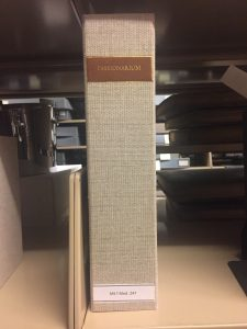 Image shows a tall enclosure covered in beige linen sitting on a shelf. There is a brown leather label towards the head of the enclosure's spine with gold tooled titling. A secondary paper label toward the tail of the enclosure's spine has the item's call number.