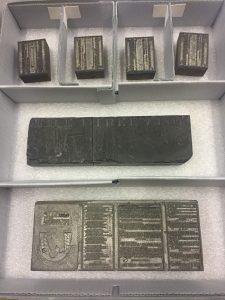 Image shows four smaller blocks of lead type and two longer blocks of lead type, each nestled in individual compartments of a larger enclosure.