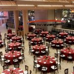 Boylston Hall set up with circular tables and red tablecloths for the Harvard Business School