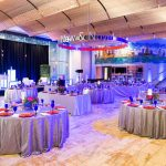 Boylston Hall set up with circular tables, silver tablecloths, and clear chairs with elaborate centerpieces